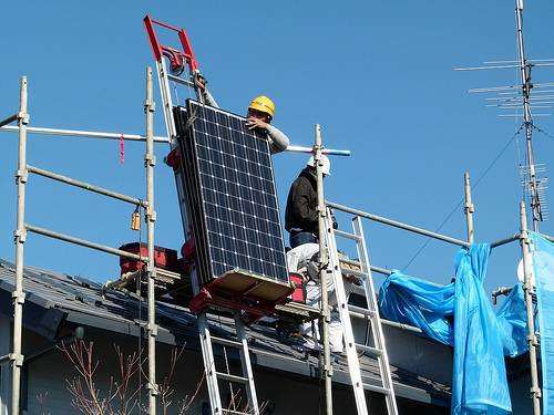 Workers installing solar panles in Japan