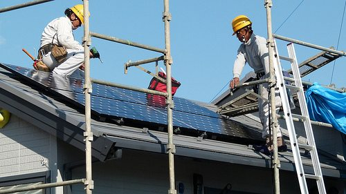 Workers installing solar panels in Japan